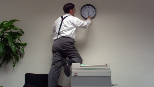 Medium shot male office employee adjusting clock forward / boss walking in / employee turning back clock / low angle