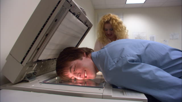 Medium shot male office worker photocopying his face / female office worker laughing at photocopies / low angle
