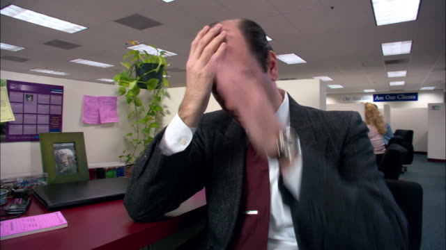 Medium shot male office worker rubbing head and sighing in cubicle / Los Angeles