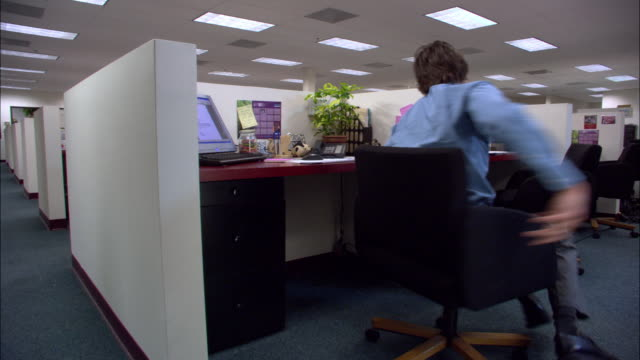 vidéos et rushes de medium shot male office worker sitting and spinning in chair in cubicle / los angeles, california - chaise
