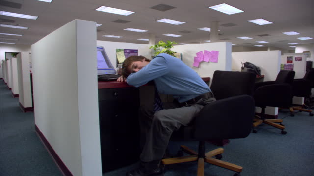 medium shot male office worker sleeping with head on desk in cubicle / los angeles, california - napping stock-videos und b-roll-filmmaterial