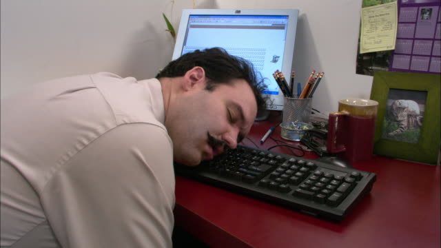 Medium shot male office worker sleeping with head on keyboard / Los Angeles