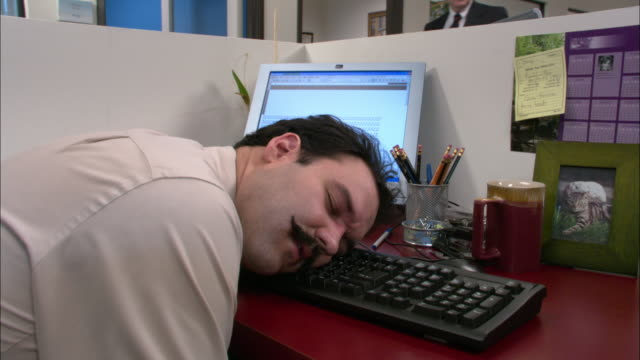 Medium shot male office worker sleeping with head on keyboard / tilt up boss looking into his cubicle / Los Angeles