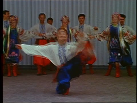 1967 medium shot male Russian folk dancer performing in squat position with rest of troupe in background / Russia