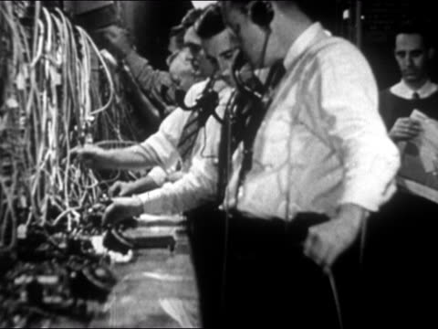 1946 medium shot male telephone operators working at switchboards - 電話交換機点の映像素材/bロール