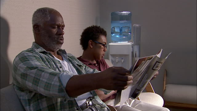 Medium shot man and boy reading magazines or catalogs in doctor's office waiting room / man holding catalog at a distance to read it