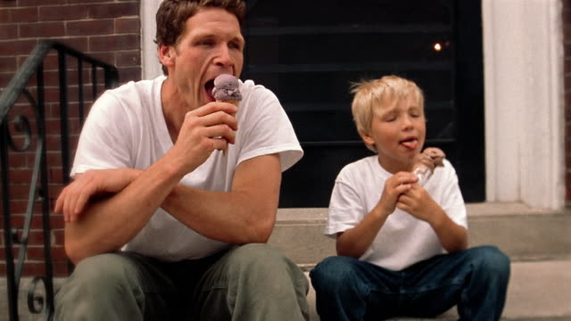 Medium shot man and boy sitting on steps + eating ice cream cones