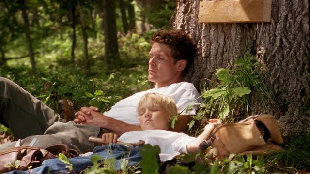 vídeos y material grabado en eventos de stock de medium shot man and boy sleeping at foot of tree in forest - dormitar