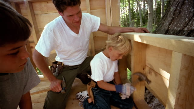 medium shot man and boy watching little boy hammer nail into treehouse - treehouse stock videos & royalty-free footage