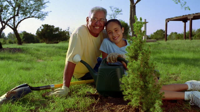 Medium shot man and girl posing with bush + watering can outdoors / New Mexico