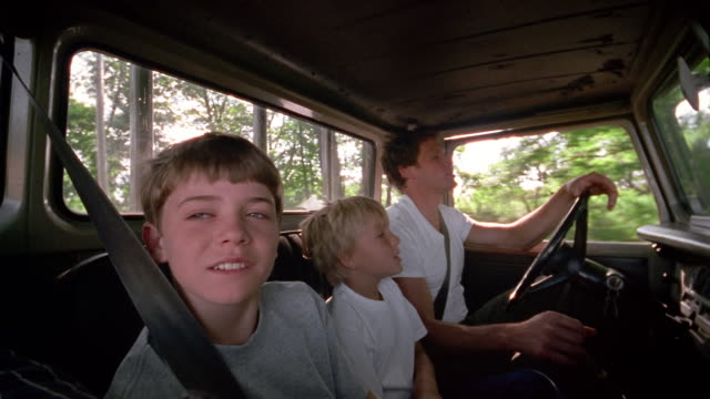 medium shot man and two boys riding in truck - シートベルト点の映像素材/bロール