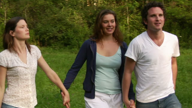 Medium shot man and two women holding hands and walking through sunlit meadow