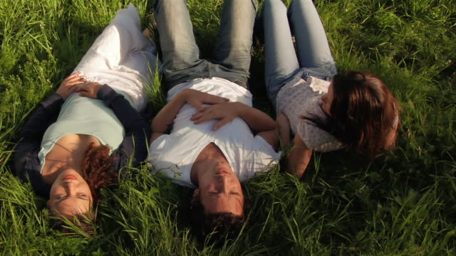 medium shot man and two women lying in grass / sun shining on them - male with group of females stock videos & royalty-free footage