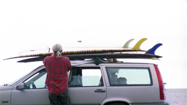 Medium shot man and two women taking surfboards off the roof of car / dog sitting in car