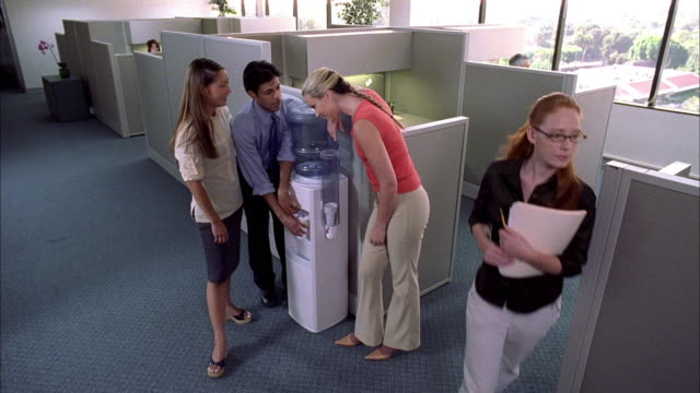 medium shot man and two women talking by water cooler in office w/cubicles - water cooler stock videos & royalty-free footage