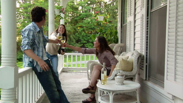 Medium shot man and two women toasting with wine on porch/ Roxbury, New York