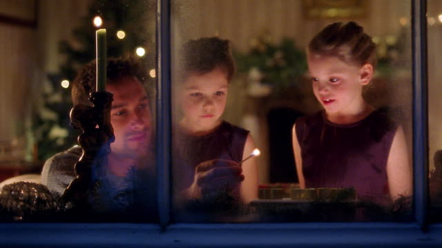 stockvideo's en b-roll-footage met medium shot man and two young girls lighting candles in window with christmas tree in background - kaars