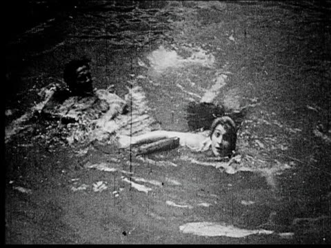 1914 B/W Medium shot Man and woman clinging to wood and swimming in sea