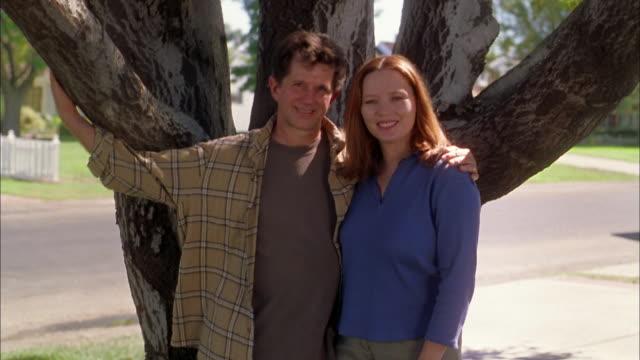 vídeos de stock, filmes e b-roll de medium shot man and woman embracing by tree outdoors + smiling at cam - de braços dados