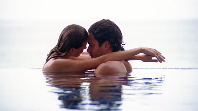 vídeos de stock, filmes e b-roll de medium shot man and woman embracing in pool - sensualidade