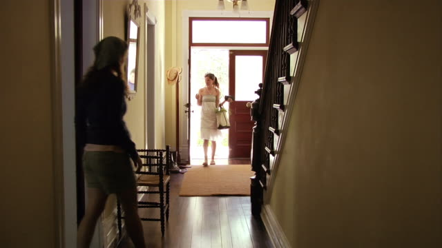 Medium shot man and woman entering front door / woman greeting them and going upstairs