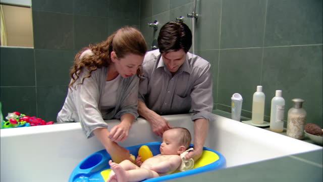 Medium shot man and woman giving baby a bath