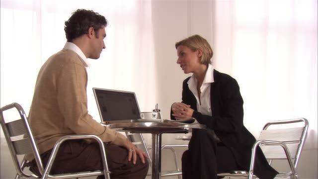medium shot man and woman having business meeting at cafe / looking at laptop - hot desking stock videos & royalty-free footage