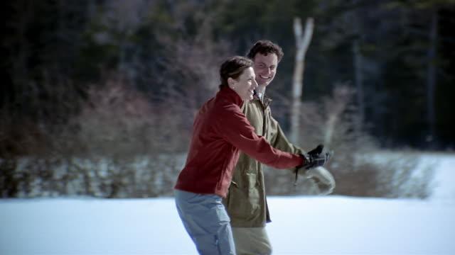 medium shot man and woman ice skating on frozen lake - ice skating stock videos & royalty-free footage