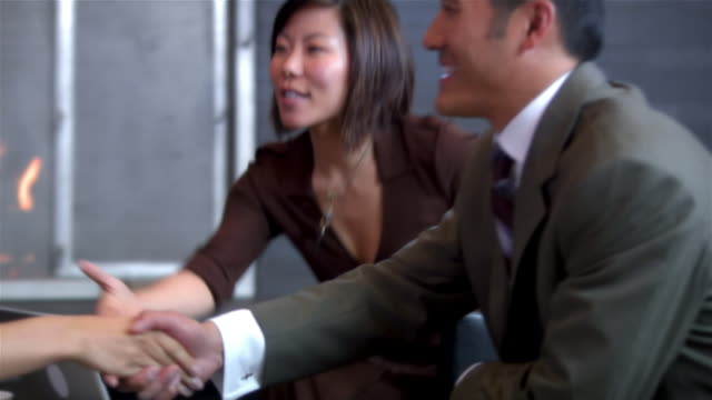 medium shot man and woman in business meeting/ leaning across table and shaking hands/ pan man and woman across table/ seattle, washington - partnership stock videos & royalty-free footage