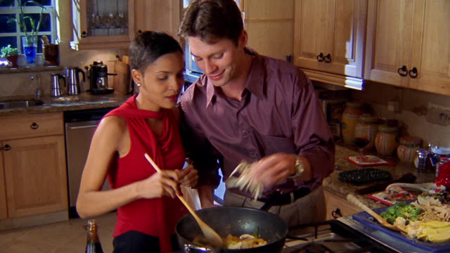 medium shot man and woman in kitchen stir-frying food in wok with man adding salt - adding salt stock videos and b-roll footage