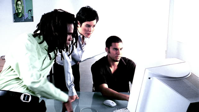 Medium shot man and woman looking over shoulder of man typing at computer in office