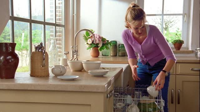 medium shot man and woman putting dishes in dishwasher / belgium - spülmaschine stock-videos und b-roll-filmmaterial