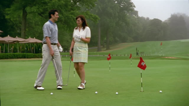 Medium shot man and woman putting on green / both missing the hole