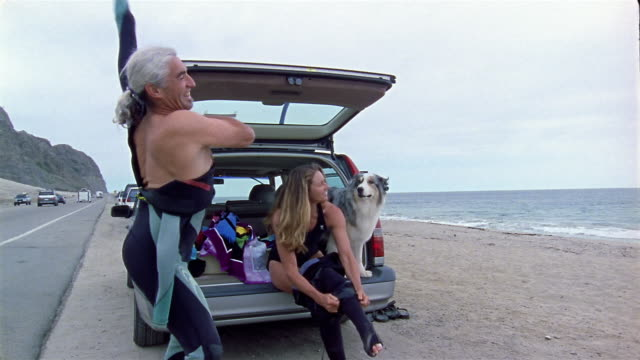 Medium shot man and woman putting on wetsuits in back of car on beach / dog sitting in back of car