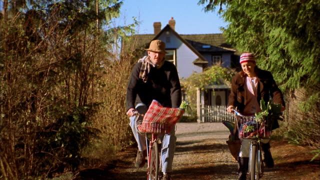 medium shot man and woman riding bicycles toward cam w/food in baskets / bainbridge island, washington - kopfbedeckung stock-videos und b-roll-filmmaterial