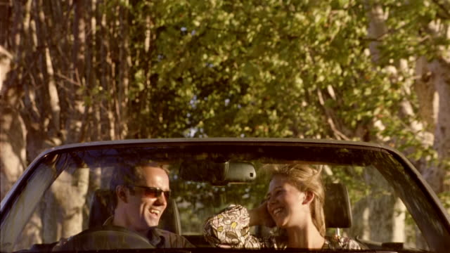 medium shot man and woman riding in convertible on tree-lined country road / talking and laughing / corsica - 年の差カップル点の映像素材/bロール