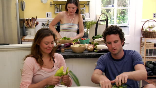 medium shot man and woman shucking corn at kitchen table as woman chops vegetables on island - husking stock videos & royalty-free footage