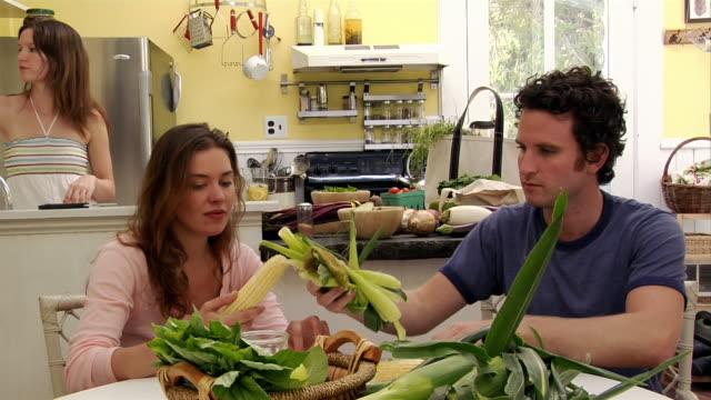 medium shot man and woman shucking corn in kitchen/ roxbury, new york - husking stock videos & royalty-free footage