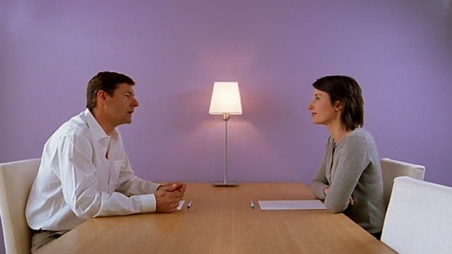 Medium shot man and woman sitting at opposite sides of conference table / arguing