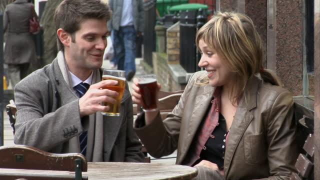 vídeos de stock e filmes b-roll de medium shot man and woman sitting down to drink beer at tables on busy sidewalk/ london - sentar se