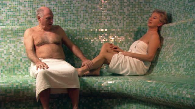 Medium shot man and woman sitting in sauna/ man rubbing woman's leg and talking