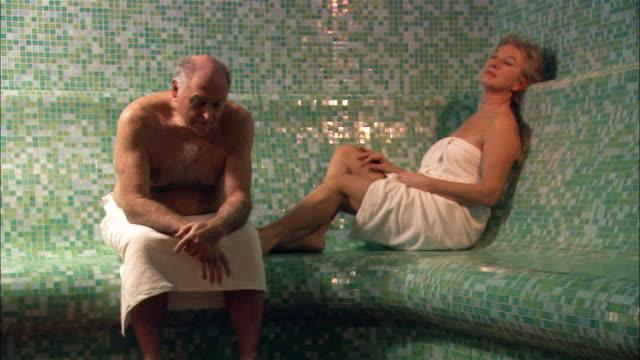 vídeos y material grabado en eventos de stock de medium shot man and woman sitting in sauna - vello pectoral