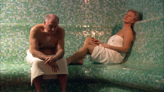 vídeos de stock, filmes e b-roll de medium shot man and woman sitting in sauna - pelo no peito