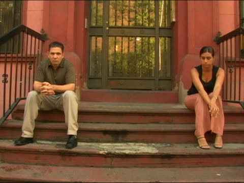 Medium shot man and woman sitting on opposite sides of stoop / glancing at one another / angry