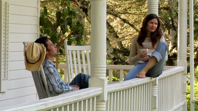 Medium shot man and woman sitting on porch of country house and drinking coffee / man in rocking chair, woman on railing
