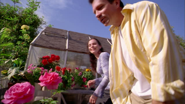 Medium shot man and woman smelling flowers while gardening on greenhouse terrace
