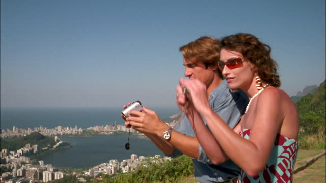 Medium shot  man and woman taking pictures w/video + still cameras on coastal cliff / Corcovado mountain / Rio