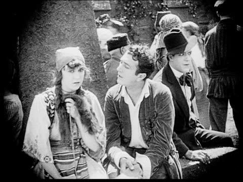 1916 b/w medium shot man and woman talking in town square as sinister man eavesdrops - 盗み聞き点の映像素材/bロール