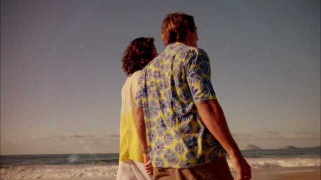 Medium shot man and woman walking arm-in-arm on beach w/city in background
