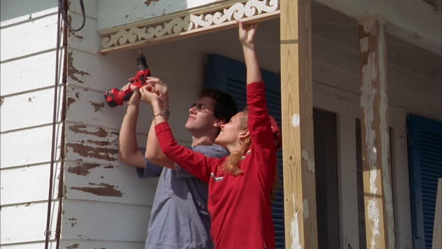 medium shot man and woman working on porch of house using drill - bricolage video stock e b–roll